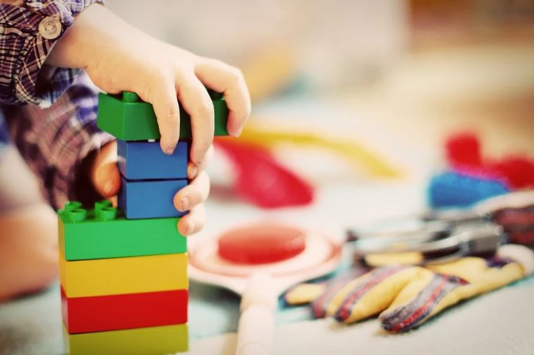 child playing with lego blocks to improve motor skills